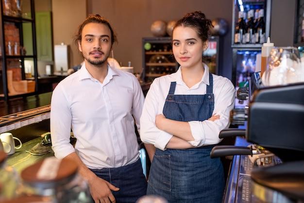 Dos jóvenes colegas con camisas blancas y delantales de mezclilla de pie junto al lugar de trabajo junto a la máquina de café en la cafetería y mirándote