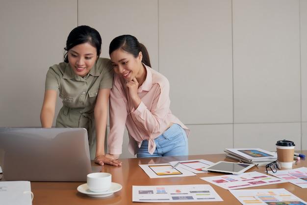 Dos jóvenes compañeras de trabajo asiáticas de pie en el escritorio y usando laptop