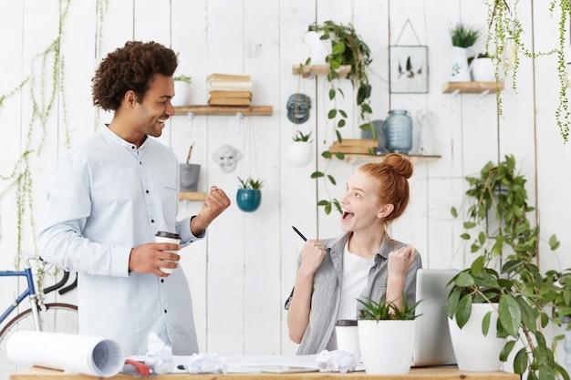 Dos jóvenes compañeros de trabajo se sienten felices y emocionados, contentos con una presentación exitosa