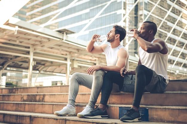 Dos jóvenes corredores se sentaron a descansar y bebieron agua juntos en las escaleras.