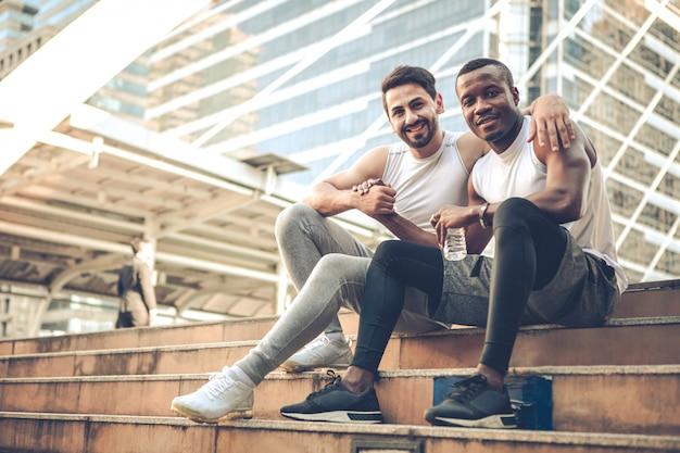 Dos jóvenes corredores se sentaron a descansar y miraban con una sonrisa en las escaleras.