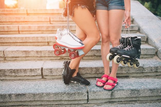 Dos jóvenes delgadas y sexys y patines. una hembra tiene patines en línea y la otra tiene patines cuádruples. las chicas cabalgan bajo los rayos del sol.