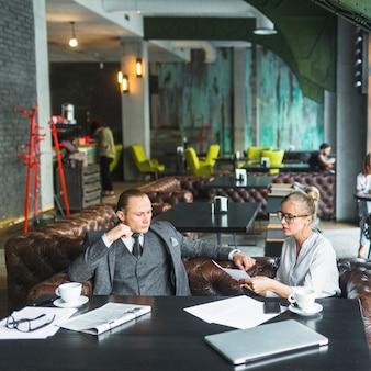 Dos jóvenes empresarios analizando documentos en el restaurante
