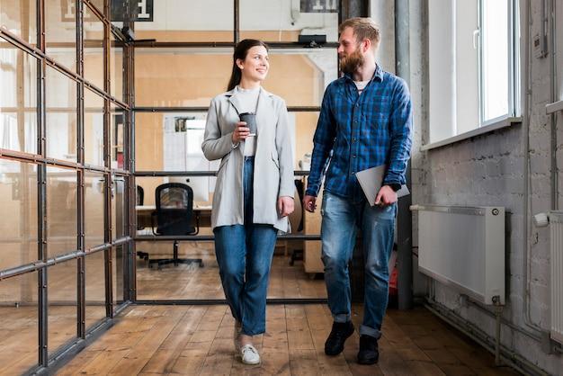 Dos jóvenes empresarios caminando juntos en la oficina