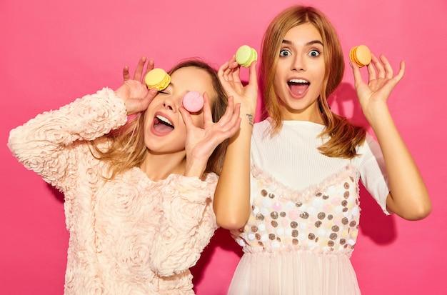 Dos jóvenes encantadoras hermosas mujeres hipster sonrientes en ropa de moda de verano. mujeres haciendo gafas, gafas con coloridos macarons, sosteniendo macarons en el lugar de los ojos. posando en pared rosa