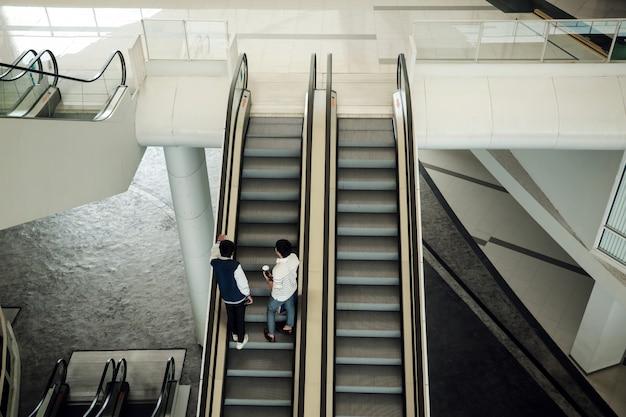 Dos jóvenes en escaleras mecánicas en la universidad moderna