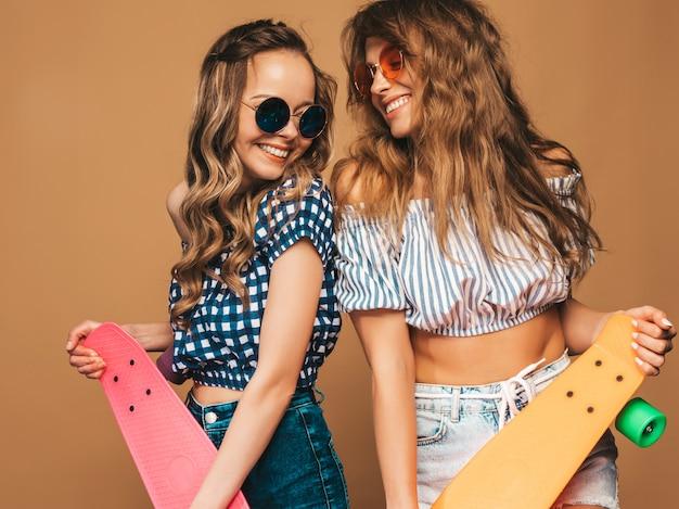 Dos jóvenes con estilo sonrientes hermosas chicas con patinetas coloridas centavo. mujeres en ropa de camisa a cuadros de verano posando. modelos positivos divirtiéndose