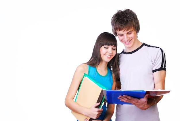 Dos jóvenes estudiantes adultos de pie cerca y leyendo