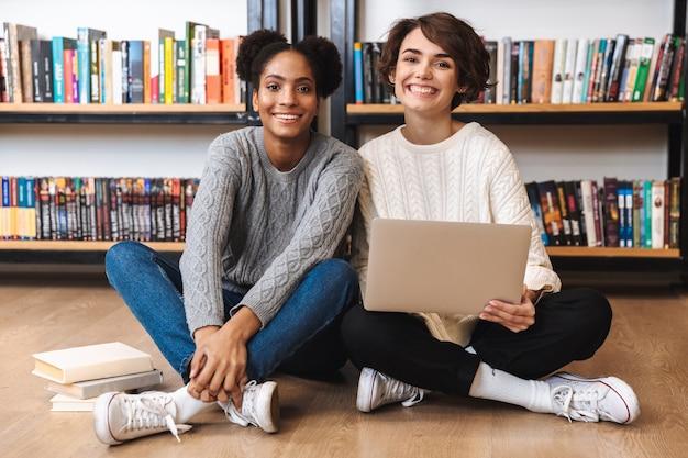 Dos jóvenes estudiantes alegres que estudian en la biblioteca, sentados en el suelo con un portátil