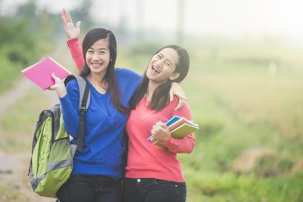 Dos jóvenes estudiantes asiáticos sosteniendo libros sonriendo brillantemente en el bosque