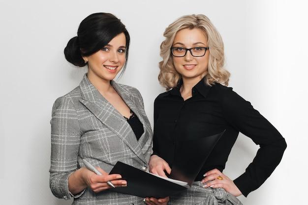 Dos jóvenes exitosas secretarias en trajes de negocios sonriendo con documentos.