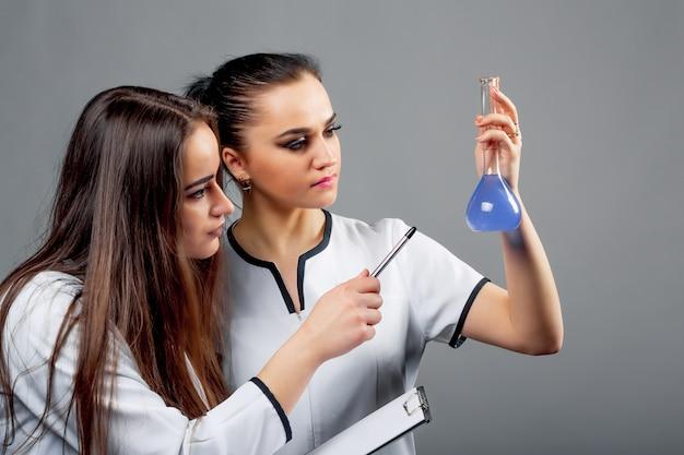 Dos jóvenes farmacéuticos con ropa médica examinando muestra líquida azul
