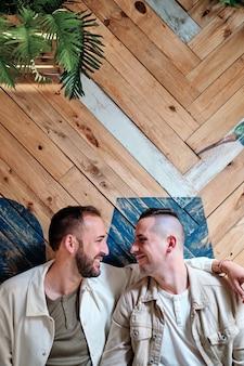 Dos jóvenes gays miran sonriendo dentro de una cafetería.