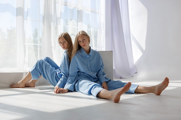 Dos jóvenes gemelas en trajes azules idénticos sentados en el piso de ciclorama blanco en estudio