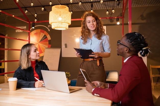 Dos jóvenes gerentes interculturales escuchando el informe de su exitoso colega en una reunión en el café