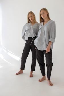 Dos jóvenes hermanas gemelas bonitas con largo cabello rubio posando en la pared blanca en ropa de gran tamaño. sesión de fotos de moda