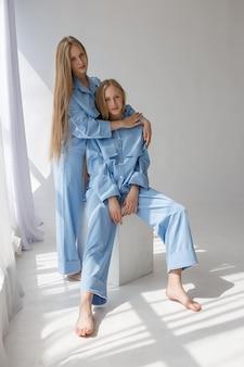 Dos jóvenes hermanas gemelas bonitas posando en trajes azules sobre blanco ciclorama de estudio