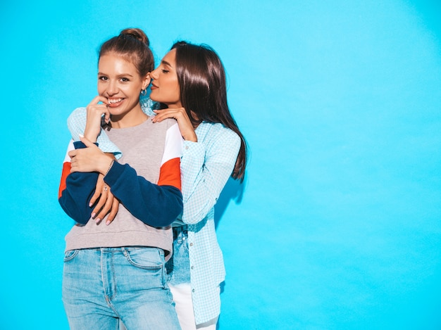 Dos jóvenes hermosas chicas hipster sonrientes en ropa casual de moda de verano. las mujeres sexy comparten secretos, chismes. aisladas en azul. mujer muerde su dedo