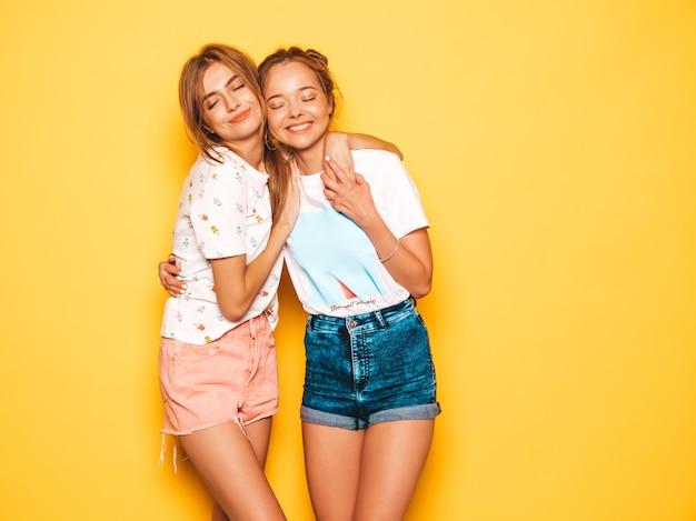 Dos jóvenes hermosas chicas hipster sonrientes en ropa de moda de verano. mujeres despreocupadas atractivas que presentan cerca de la pared amarilla. modelos positivos volviéndose locos y divirtiéndose.