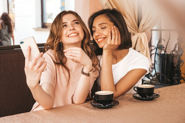 Dos jóvenes hermosas chicas hipster sonrientes en ropa de moda de verano. mujeres despreocupadas charlando en la terraza terraza café y tomando café. modelos positivos divirtiéndose y comunicándose