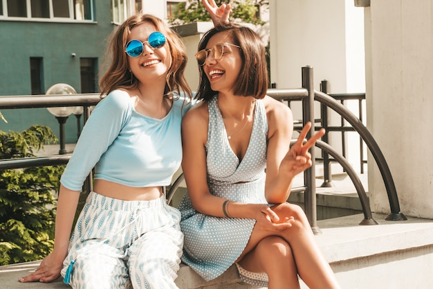Dos jóvenes hermosas chicas hipster sonrientes en ropa de moda de verano. mujeres despreocupadas sexy posando en el fondo de la calle en gafas de sol. modelos positivos divirtiéndose y volviéndose locos