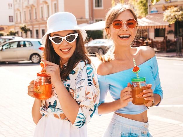 Dos jóvenes hermosas chicas hipster sonrientes en ropa de moda de verano y sombrero de panamá.