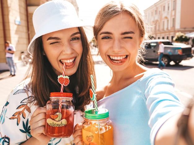 Dos jóvenes hermosas chicas hipster sonrientes en ropa de moda de verano