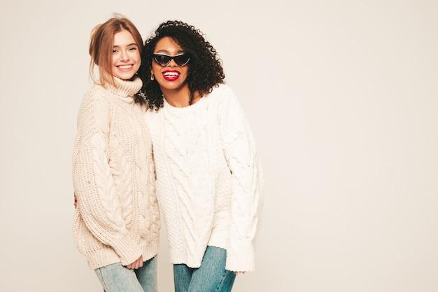Dos jóvenes hermosas chicas hipster sonrientes en suéteres de invierno de moda. modelos positivos divirtiéndose y abrazándose.