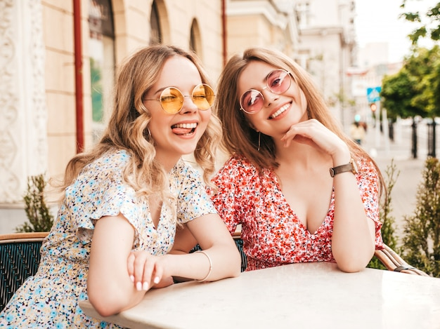 Dos jóvenes hermosas chicas hipster sonrientes en vestido de verano de moda. mujeres despreocupadas charlando en el café de la terraza en el fondo de la calle con gafas de sol. modelos positivos divirtiéndose y comunicándose