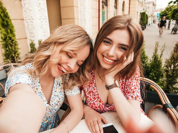 Dos jóvenes hermosas chicas hipster sonrientes en vestido de verano de moda. mujeres despreocupadas charlando en el café de la terraza en el fondo de la calle. modelos positivos divirtiéndose y tomando selfie en teléfono inteligente