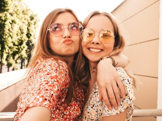 Dos jóvenes hermosas chicas hipster sonrientes en vestido de verano de moda. mujeres despreocupadas sexy posando en el fondo de la calle en gafas de sol. ellos toman fotos de autorretratos en el teléfono inteligente al atardecer