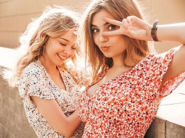 Dos jóvenes hermosas chicas hipster sonrientes en vestido de verano de moda. mujeres despreocupadas sexy posando en el fondo de la calle. modelos positivos divirtiéndose y mostrando signos de paz