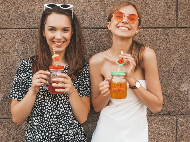 Dos jóvenes hermosas chicas hipster sonrientes en vestidos de moda de verano.