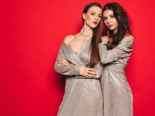 Dos jóvenes hermosas chicas morenas en bonito vestido brillante de verano de moda