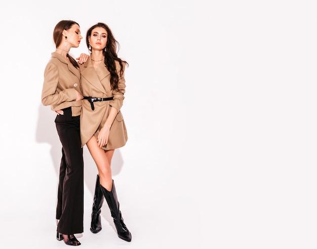 Dos jóvenes hermosas chicas morenas en ropa de verano agradable y femenina. mujeres abrazarse