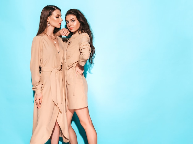 Dos jóvenes hermosas chicas morenas en ropa de verano agradable. mujeres despreocupadas sexy posando junto a la pared azul en el estudio