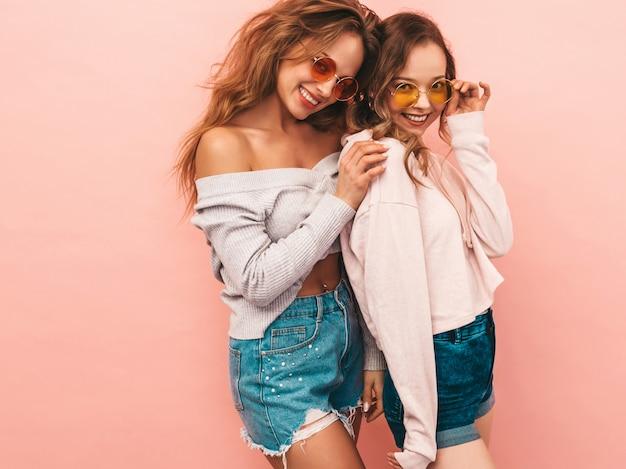 Dos jóvenes hermosas chicas sonrientes en ropa de moda de verano. sexy mujer despreocupada posando. modelos positivos divirtiéndose