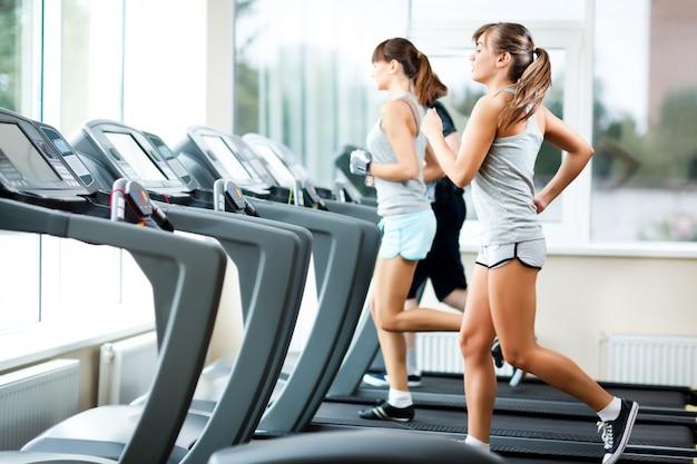 Dos jóvenes hermosas mujeres delgadas en ropa deportiva corriendo en cintas de correr en el gimnasio