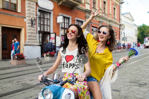 Dos jóvenes hermosas mujeres hipster montando en moto calle de la ciudad