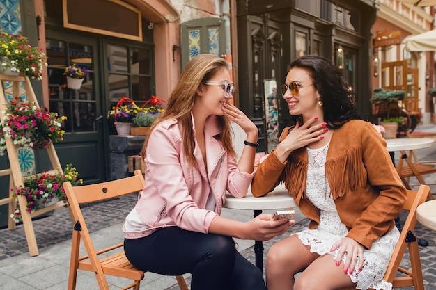 Dos jóvenes hermosas mujeres hipster sentados en el café