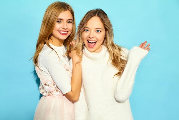 Dos jóvenes hermosas mujeres hipster sonrientes en ropa de moda verano blanco. mujeres despreocupadas sexy posando junto a la pared azul. modelos positivos abrazando