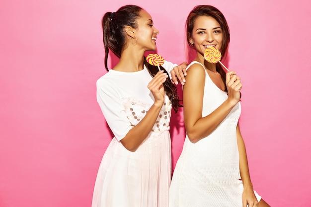 Dos jóvenes hermosas mujeres morenas sonrientes en ropa de moda de verano. mujeres calientes despreocupadas que presentan cerca de la pared rosada. modelos divertidos positivos con piruleta