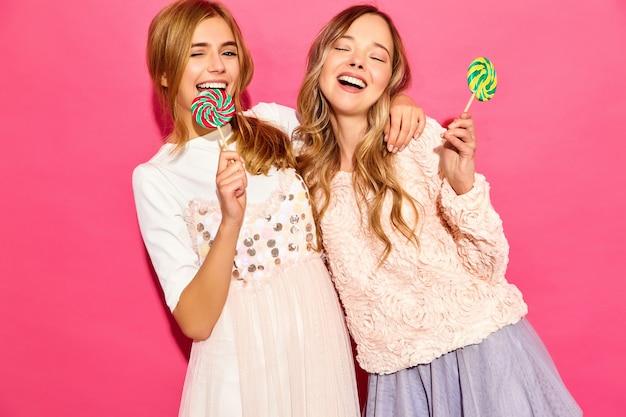 Dos jóvenes hermosas mujeres rubias hipster sonrientes en ropa de moda de verano. mujeres calientes despreocupadas que presentan cerca de la pared rosada. modelos divertidos positivos abrazándose con piruleta