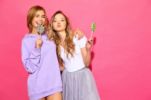 Dos jóvenes hermosas mujeres rubias hipster sonrientes en ropa de moda de verano. mujeres calientes despreocupadas que presentan cerca de la pared rosada. modelos divertidos positivos con piruleta, guiñando un ojo
