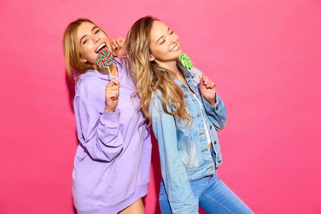 Dos jóvenes hermosas mujeres rubias hipster sonrientes en ropa de moda de verano. mujeres calientes despreocupadas que presentan cerca de la pared rosada. modelos divertidos positivos con piruleta