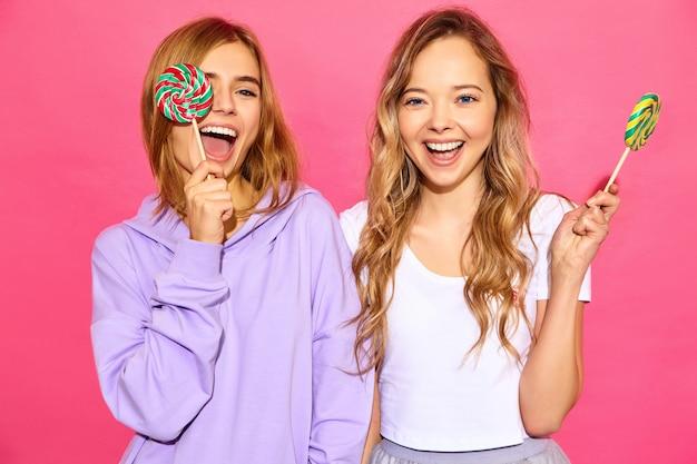 Dos jóvenes hermosas mujeres rubias hipster sonrientes en ropa de moda de verano. mujeres calientes despreocupadas que presentan cerca de la pared rosada. los modelos positivos cubren los ojos con piruleta