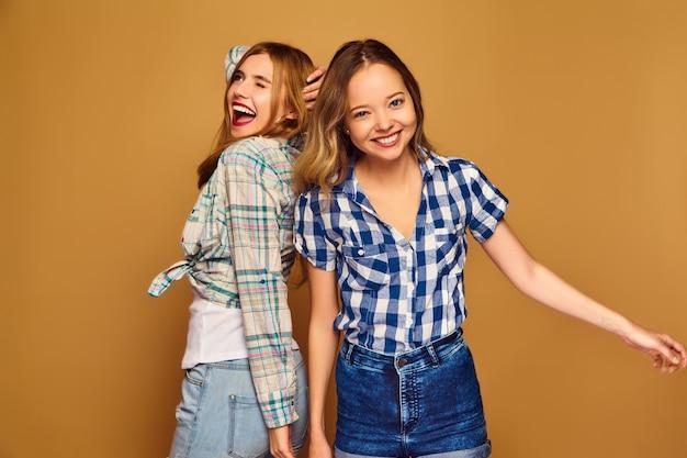 Dos jóvenes hermosas rubias sonrientes en camisas a cuadros de verano de moda