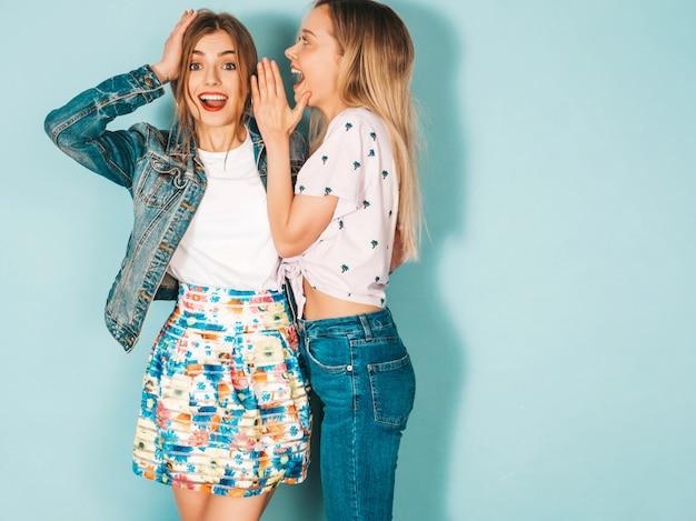 Dos jóvenes hermosas rubias sonrientes chicas hipster en ropa casual de moda de verano.