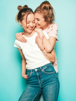 Dos jóvenes hermosas rubias sonrientes chicas hipster en ropa de jeans de moda hipster de verano. mujeres despreocupadas sexy posando junto a la pared azul. modelos modernos y positivos divirtiéndose