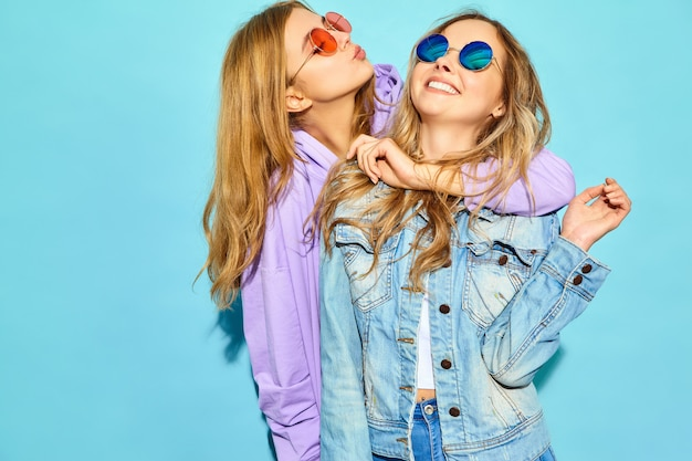 Dos jóvenes hermosas rubias sonrientes mujeres hipster en ropa de moda de verano. mujeres despreocupadas sexy posando junto a la pared azul en gafas de sol. modelos positivos volviéndose locos y abrazándose